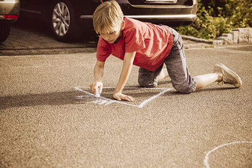 Boy using sidewalk chalk in his neighborhood - MFF001943