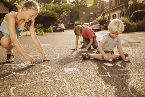Children using sidewalk chalk in their neighborhood - MFF001946