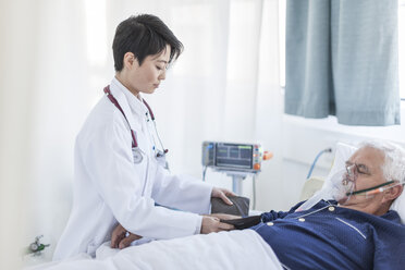 Doctor taking blood pressure of senior man with oxygen mask in a hospital - ZEF006267