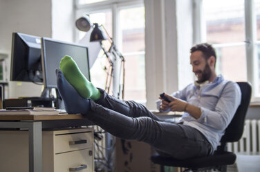 Young man in office with feet on desk wearing different socks - FKF001202
