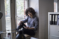 Young woman in office sitting at the window - FKF001313