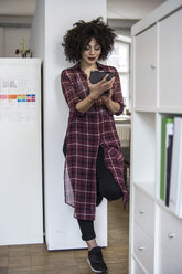 Young woman in office using digital tablet - FKF001226