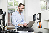 Smiling young man in office sitting on desk using laptop - FKF001238
