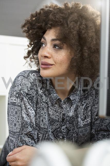 Smiling young woman in office at desk looking sideways - FKF001249 - Florian Küttler/Westend61