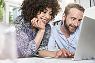 Smiling man and woman in office sharing laptop - FKF001252