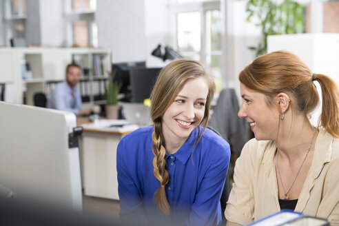 Two smiling women in office looking at each other - FKF001255