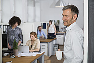 Smiling man in office with colleagues in background - FKF001272