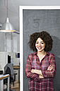 Smiling young woman standing at blackboard in office - FKF001292