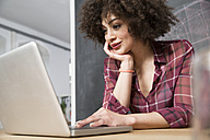 Young woman in office using laptop - FKF001298