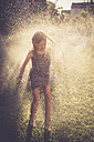 Girl having fun with splashing water in the garden - SARF002060