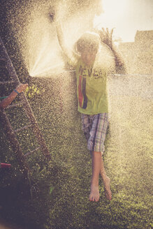 Boy and girl having fun with splashing water in the garden - SARF002061