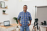 Portrait of smiling young man in his photographic studio - EBSF000769