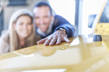 Couple examining new car at car dealership - ZEF006901