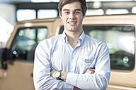 Portrait of confident car dealer in showroom - ZEF006903