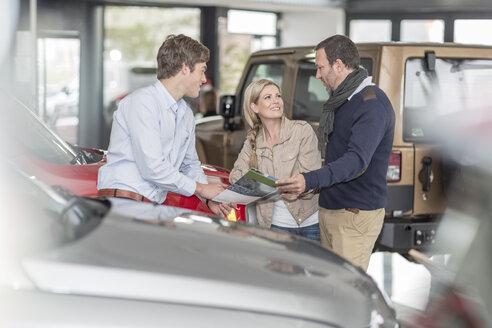 Car dealer talking to couple in showroom - ZEF006910