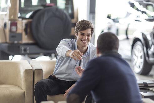 Car dealer giving key to client - ZEF006919