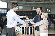 Car dealer giving key to client - ZEF006921