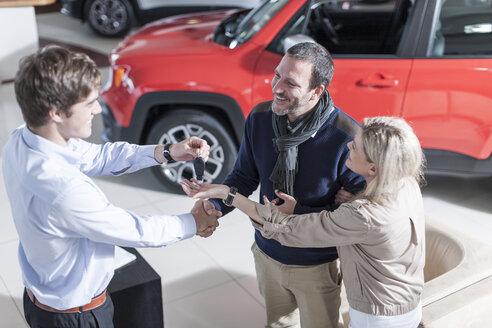 Car dealer giving key to client - ZEF006924