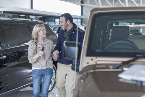 Happy couple at car dealership hand in hand at new car - ZEF006927