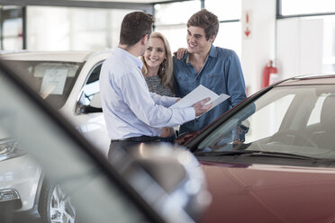 Car dealer showing brochure to young couple in showroom - ZEF006945