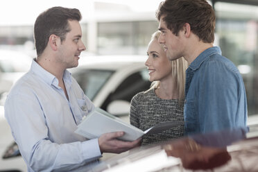 Car dealer showing brochure to young couple in showroom - ZEF006947