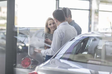 Car dealer showing brochure to young couple in showroom - ZEF006955