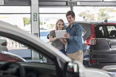 Young couple with digital tablet at car dealership - ZEF006956