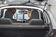 Young couple sitting in new car at car dealership - ZEF006958