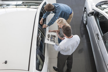 Car dealer showing brochure to young couple in showroom - ZEF006961