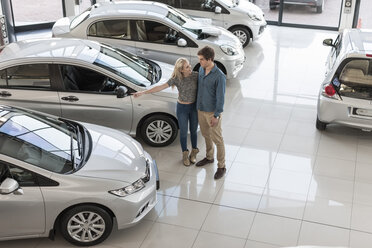 Young couple looking at new cars at car dealership - ZEF006964