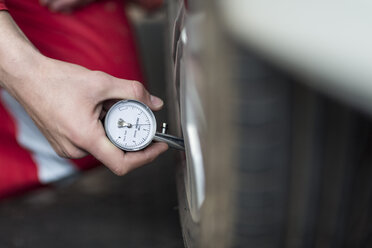 Car mechanic at work in repair garage, tyre pressure gauge - ZEF006978