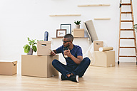 Young man sitting beside cardboard boxes having a coffee break - EBSF000804
