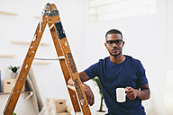 Young man leaning on step ladder having a coffee break - EBSF000821