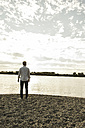 Young man standing by the riverside - UUF004985