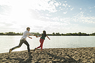 Young couple running hand in hand by the riverside - UUF004993