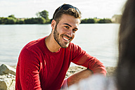 Young man smiling at woman by the riverside - UUF005013