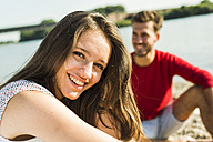 Portrait of happy young woman with man by the riverside - UUF005016
