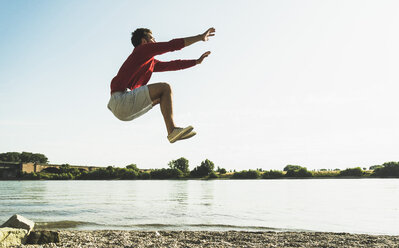 Young man jumping mid-air by the riverside - UUF005020