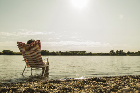 Young woman sitting on deckchair in river - UUF005022