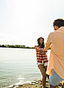 Carefree young couple hand in hand by the riverside - UUF005026