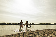 Young couple running with inner tubes in river - UUF005032