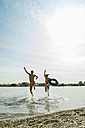 Young couple running with inner tube in river - UUF005038