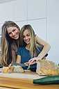 Mother and daughter in kitchen cutting bread - CHAF000840