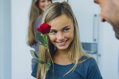 Smiling girl with parents holding rose - CHAF000853