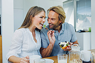 Happy couple eating at kitchen table - CHAF000861
