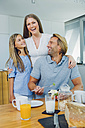 Happy mother, father and daughter at kitchen table - CHAF000864