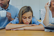 Frustrated girl with distracted parents at table - CHAF000972