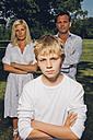 Portrait of boy with arms crossed and his parents in the background - CHAF000922