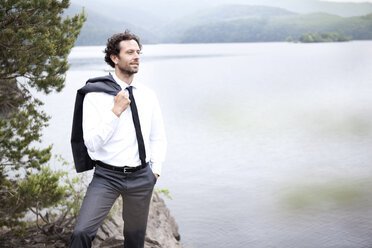 Germany, Rur Reservoir, relaxed businessman at lakeshore - MFRF000242