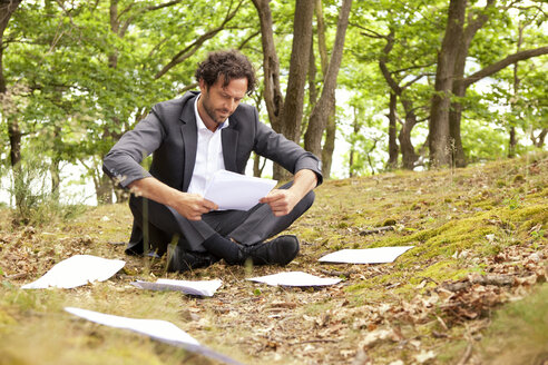 Germany, businessman sitting in forest reading documents - MFRF000248